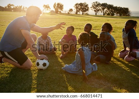 Elementary school kids and teacher sitting with ball in field