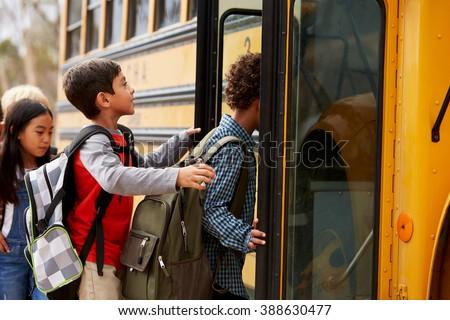 Elementary school kids climbing on to a school bus