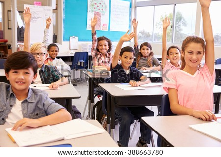 Elementary school kids in a classroom raising their hands
