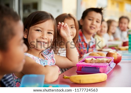 Elementary school kids sitting a table with  packed lunches