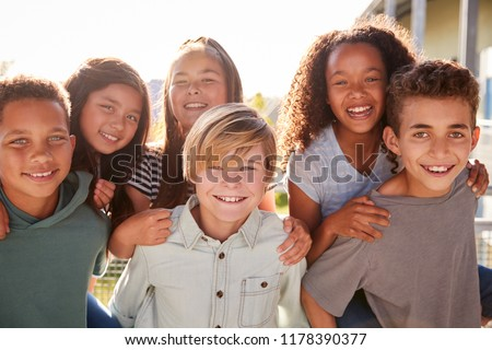 Elementary school kids smiling to camera during school break