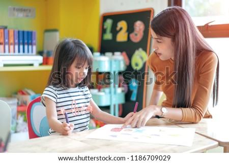 elementary school kids studying with her teacher in elementary school  #1186709029