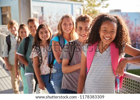 Elementary school kids with backpacks smiling at the camera