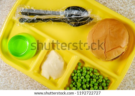 Elementary school lunch cheeseburger with mashed potatoes gelatin and green peas on portion tray