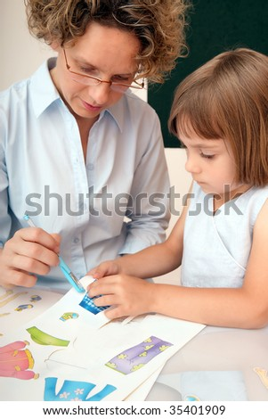 Elementary school pupil working under the supervision of a educator