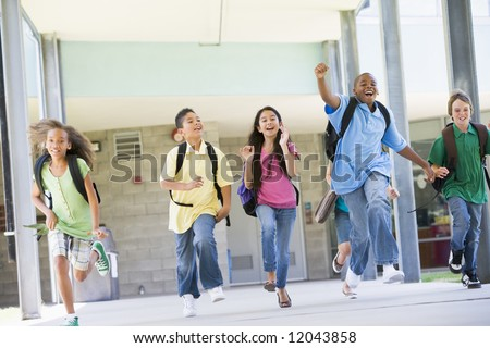 Elementary school pupils running outside together