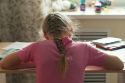 Elementary school student doing homework. Education concept. Back, rear view. Modern hairstyle - pigtail. Girl braided a pigtail.