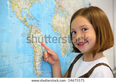 Elementary school student smiles by world map