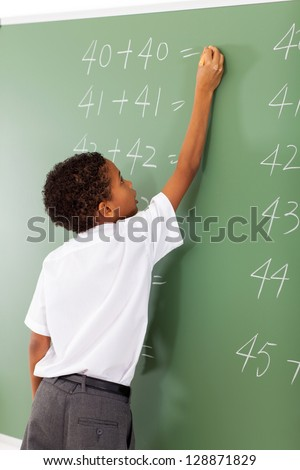 elementary school student writing maths answer on chalkboard