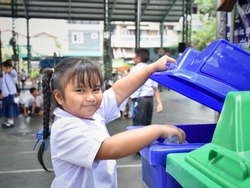 Elementary school students are throwing garbage into the bin with a smiling face.