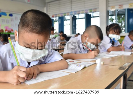 Elementary school students wearing hygienic mask while studying in the classroom.