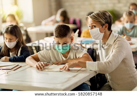 Elementary school teacher helping her student with learning during a class in the classroom. They are wearing protective face masks due to coronavirus pandemic.