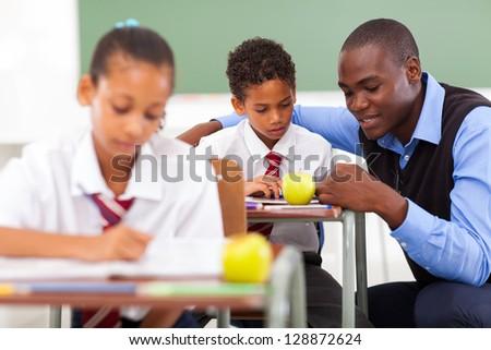 elementary school teacher helping student in classroom