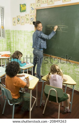 Elementary school teacher standing at a chalkboard writing as she smiles at her students writing at their desks. Vertically framed photo.