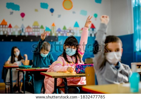 Elementary schoolchildren wearing a protective face masks  in the classroom. Education during epidemic. Photo stock ©