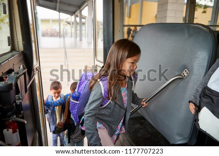 Elementary schoolgirl getting on the school bus to go home