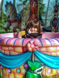 Elementary smiling girl in a coat on a merry-go-round at a city fair showing her ticket