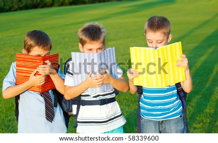 Elementary students with books in park