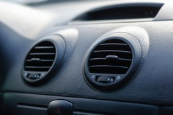 Elements of a car air conditioning. Details of the front panel of the car with air diffusers and an emergency stop button. The interior of the car. Shooting from the rear seat toward the windshield