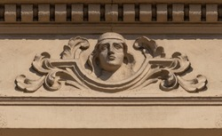 Elements of architectural decoration of buildings, stucco patterns with flowers and faces, gypsum ornaments and wall textures. On the streets in Barcelona, ​​public places.