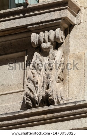 Elements of architectural decorations of buildings, a beam, a bracket under the balcony and a column, plaster patterns and stucco. On the streets in Catalonia, public places. #1473038825