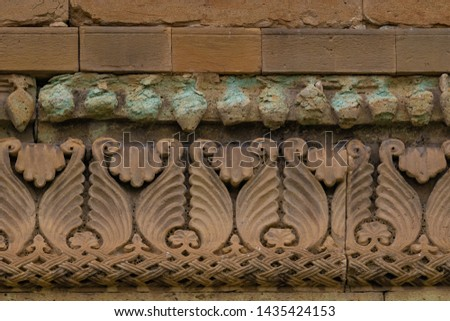 Elements of architectural decorations of buildings, gypsum stucco, wall texture, plaster ornaments and patterns. On the streets in Georgia, public places. #1435424153