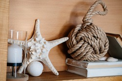 Elements of decor in the sea style. candlestick, starfish and a tangle of ropes on the books. Interior design.