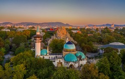 Elephant house. Old building in the city park with rocks. green area, real lights, no filter. cityscape in the background Europe, Hungary, Budapest, City park of Budapest, Budapest zoo