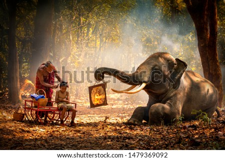Elephant mahout portrait. Grandfather was cutting his nephew with an elephant holding a mirror. vintage style. The activities at Krapho, Tha Tum District, Surin, Thailand. #1479369092