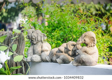 Elephant stone statue sit on white wall with green leaves background Photo stock ©