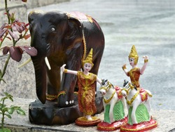 Elephants carved from wood, male and female dolls in Thai traditional dance costumes and horse dolls placed on granite tile floors.