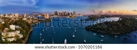 Elevated aerial panorama over Berry bay waters on Sydney harbour in view of city CBD landmarks connected by the Sydney harbour bridge at sunset. #1070201186