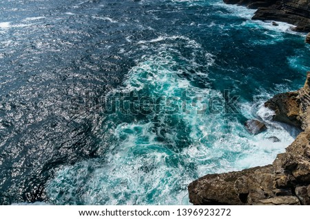 Elevated, birds eye view of ocean water surface with tough waves and cliff rocks. Nature texture background #1396923272