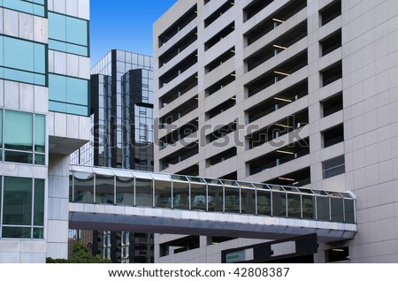 Elevated glass-covered city walkway between a tall office building and a tall parking garage.