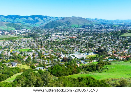 Elevated scenic view of San Luis Obispo urban area sprawl and green mountains of Santa Lucia Range from Bishop Peak Trail on sunny spring day. Foto stock ©