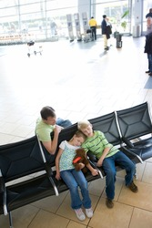 Elevated slanted shot of a father sitting beside children in airport departure lounge with boy and girl sleeping.