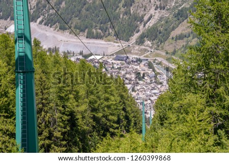 Elevated view from a cable car of a mountain valley in summer with an alpine village and green forest, Cogne, Aosta Valley, Alps, Italy #1260399868