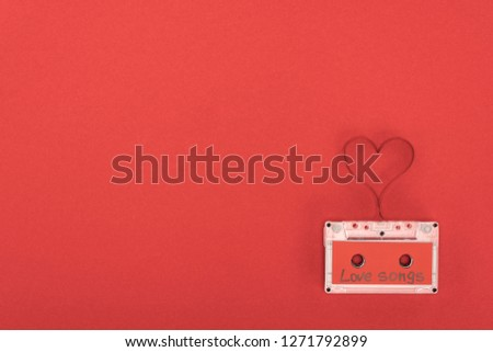 elevated view of audio cassette with lettering love songs and heart symbol made of tape isolated on red, st valentine day concept