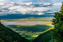 Elevated view of floor of Ngorongoro Crater from the southern edge of the crater.  Looking toward Lerai Forest and the alkaline crater lake, Lake Magadi, with clouds covering the rim on other side.