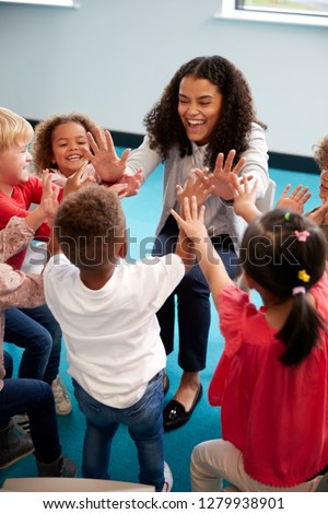 Elevated view of infant school children in a circle in the classroom giving high fives to their smiling female teacher, vertical, close up