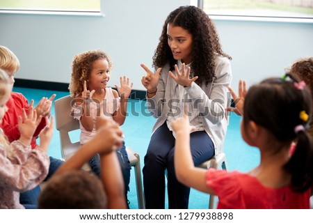 Elevated view of infant school children sitting on chairs in a circle in the classroom, raising hands and learning to count with their female teacher, close up