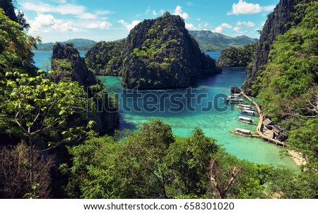 Elevated view of lagoon with boats surrounded by rocks and turquoise sea. Coron. Palawan - Shutterstock ID 658301020