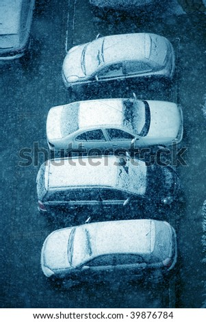 elevated view of snow covered cars in parking lot