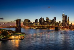 Elevated view of the Brooklyn Bridge and Lower Manhattan skyscrapers at dusk. The illuminated skyline of the Financial District reflects in the East River. New York City.
