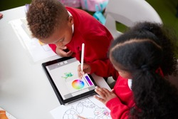 Elevated view of two kindergarten school kids sitting at a desk in a classroom drawing with a tablet computer and stylus, close up