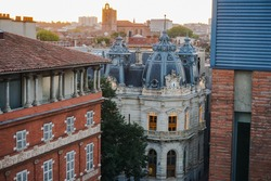 Elevated views at dawn over some old buildings in Languedoc Street, in the historic neighborhood of Carmes in Toulouse, France, with the bell tower of Saint Stephen's (Saint-Étienne) Cathedral afar