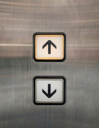 Elevator buttons for up and down with arrows. The buttons are placed on polished stainless steel plate.  Orange light is turned on on the up sign requesting for going upper floor.