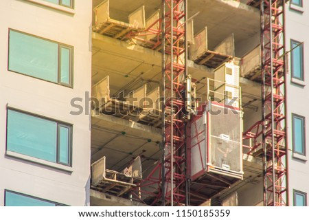 Elevator in high building construction site for transport construction workers up unfinished buildings. Passenger and material hoist transport platform for vertical transportation of man and material.