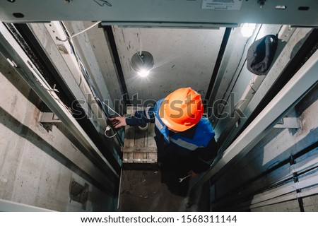 Elevator operator in the Elevator shaft makes repairs