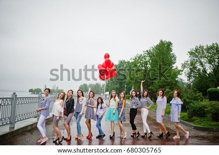 Eleven amazingly-looking braidsmaids with stunning bride posing with red heart-shaped balloons on the pavement against the lake in the background. #680305765